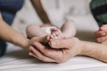 Mutter und Vater halten Füße des kleinen Jungen, Teilsicht — Stockfoto