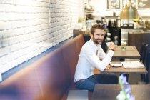 Geschäftsmann sitzt mit Tasse Kaffee im Café — Stockfoto