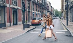 Two women holding shopping bags crossing the street in the city — Stock Photo