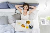 Woman sitting in bed with breakfast tray, elevated view — Stock Photo
