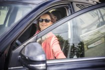 Portrait of woman wearing sunglasses getting on her car — Stock Photo
