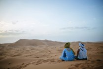 Woman sitting in the desert with Berber guide, watching sunset — Stock Photo