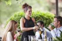 Waitress showing wine bottle to clients in restaurant — Stock Photo