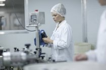 Woman cleaning flask in pharmaceutical plant — Stock Photo