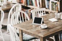Mesa en un café con taza de café y tableta digital - foto de stock