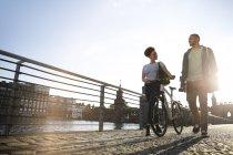 Couple marchant au bord de la rivière, poussant vélo — Photo de stock
