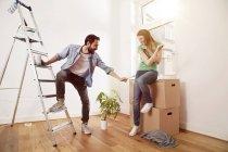 Playful young couple renovating an apartment — Stock Photo
