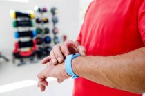 Man in fitness gym with smartwatch — Stock Photo