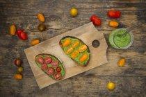 Rebanadas de pan tostado con pesto y tomate sobre tabla de madera, vista superior - foto de stock