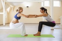 Prenatal yoga, female yoga instructor, stretching — Stock Photo