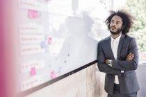 Homme d'affaires en regardant tableau blanc — Photo de stock