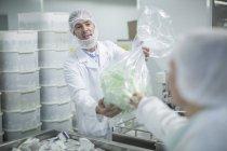 Assistente di laboratorio in pianta farmaceutica consegnando il sacchetto di plastica — Foto stock