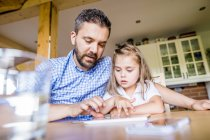 Father and daughter sitting at home using digital tablet — Stock Photo