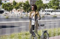 Woman pushing bicycle in city — Stock Photo
