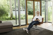 Uomo che si siede con tavoletta sulla sedia nel suo salotto — Foto stock