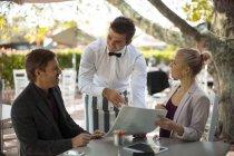 Paar im Restaurant im Freien sitzen servierfertig Kellner — Stockfoto