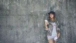 Молодая женщина прислонилась к бетонной стене, слушая музыку с наушниками — стоковое фото