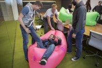 Gruppo di gente di affari giocando intorno con divani gonfiabili — Foto stock