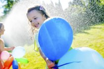 Little girl with balloons having fun with lawn sprinkler in the garden — Stock Photo