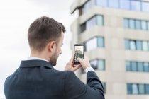 Homme d'affaires prenant une photo de téléphone portable — Photo de stock