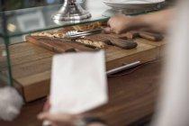 Donna che serve rotolo con tong pasticceria — Foto stock