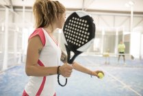Female paddle tennis player on court with man in background — Stock Photo