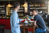 Kellner serviert Cappuccino in einem café — Stockfoto
