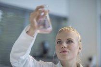 Jovem mulher no laboratório examinando o líquido no balão de Erlenmeyer — Fotografia de Stock