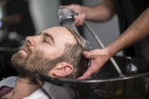 Customer laid back as he gets his hair washed at barbershop — Stock Photo