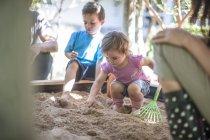Fille avec la famille, jouer dans le bac à sable — Photo de stock