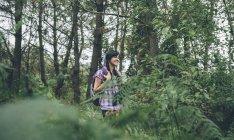 Улыбающаяся молодая женщина с рюкзаком гуляет по лесу — стоковое фото