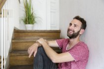 Smiling young man sitting on stairs — Stock Photo