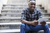 Человек сидит на лестнице и с помощью планшета — стоковое фото