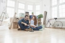 Couple surrounded by cardboard boxes sitting on floor — Stock Photo