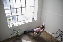 Homme assis sur une chaise et rêvant dans un bâtiment moderne — Photo de stock