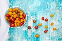 Tomates frescos coloridos en tazón de fuente - foto de stock