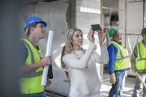 Construction workers and woman on construction site — Stock Photo