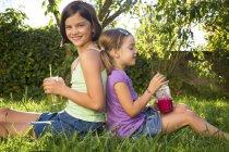 Дві маленькі сестри, сидячи спиною до спини на луг та пили коктейлі — стокове фото