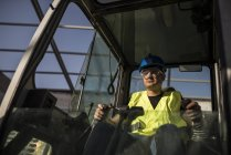 Construction worker working in caterpillar — Stock Photo