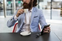 Businessman holding cell phone in cafe — Stock Photo