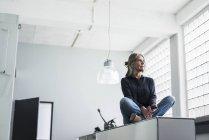 Mulher sênior sentada em um armário — Fotografia de Stock