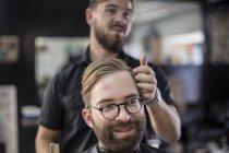 Professional barber and customer smiling at barbershop — Stock Photo