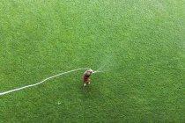 Мальчик, стоящий на газоне и играющий со шлангом — стоковое фото