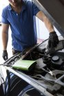 Mechanic refilling oil in a car — Stock Photo