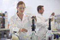 Jeune femme caucasienne travaillant en laboratoire — Photo de stock