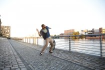 Young man throwing stone into river — Stock Photo