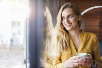 Smiling woman in a coffee shop — Stock Photo