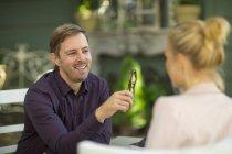 Man smiling at woman at outdoor restaraunt — Stock Photo