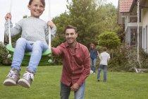 Vater schubst Tochter auf Schaukel im Garten — Stockfoto