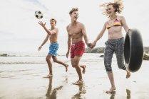 Amici che corrono con una palla e uno pneumatico sulla spiaggia — Foto stock